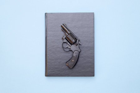 Book and gun on a blue background