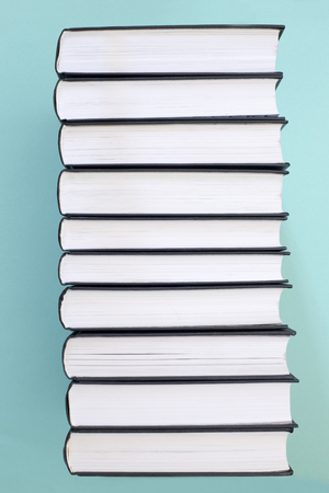A stack of books on a green background, side view
