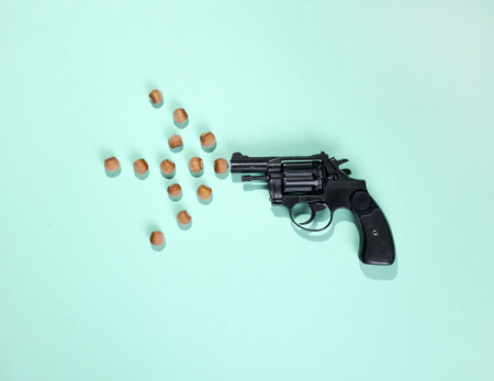 Pistol and hazelnuts on a green background, top view