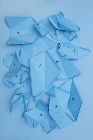 Details and parts of the papercraft scheme for assembling paper or cardboard figures on a blue background Reklamní fotografie