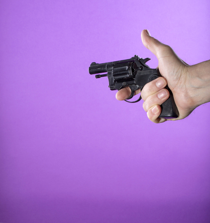 Revolver in a mans hand on a purple background Stok Fotoğraf
