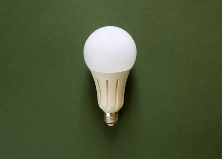 New powerful energy-saving, LED light bulb on a green background Banque d'images - 99364617