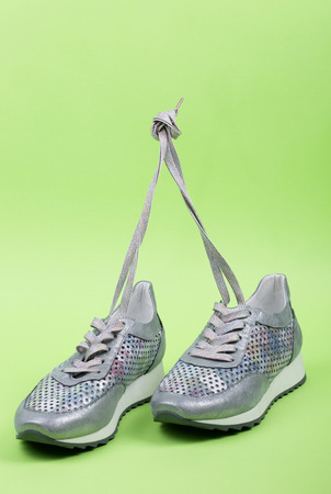 Gray Womens sneakers on a green background Stock Photo