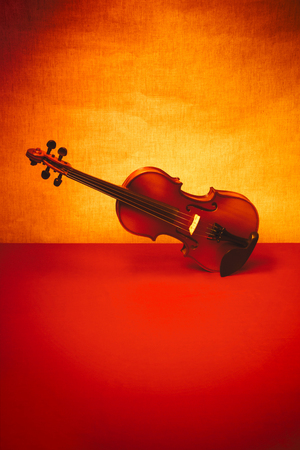 Still life with a violin on a red table. Minimalism.
