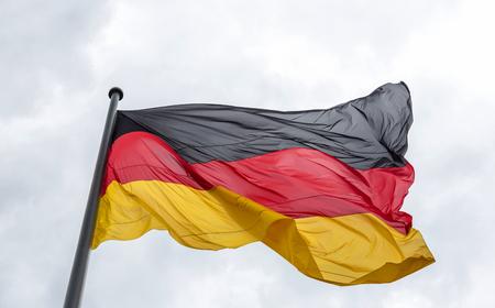 Die Nationalflagge der Bundesrepublik Deutschland hat sich im Wind gegen den Himmel entwickelt Standard-Bild
