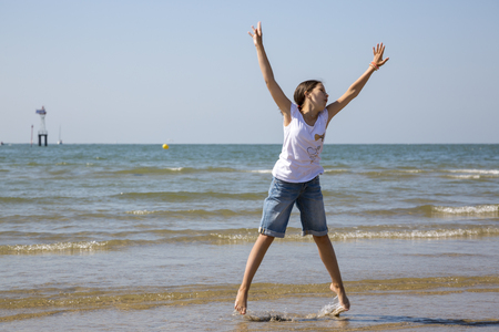 Happy jumping up girl on the shore of the English Channel