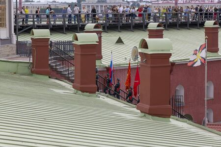 St. Petersburg, Russia - August 11, 2018: Solemn removal of the flag of the Russian Federation and the flag of St. Petersburg in the Peter and Paul Fortress in St. Petersburg Редакционное