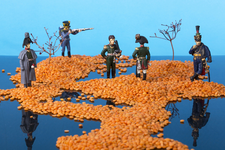 Landscape with islands in the sea and the soldiers of the Napoleonic wars. Installation of grains of lentils, branches of plants and tin soldiers. Stock Photo