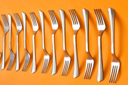 Abstract still life with forks on orange background Stock Photo