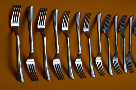 Abstract still life with forks on brown background