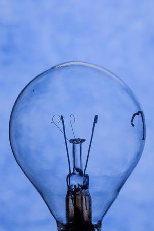 Burnt light bulb on blue background close up Фото со стока