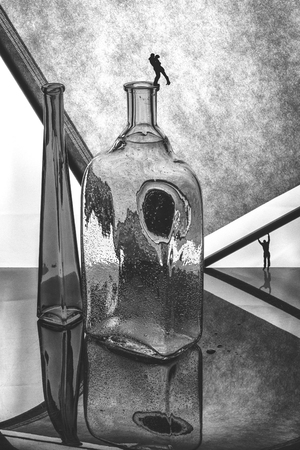 Black and white still life with glass bottles and silhouettes of people. Love story.