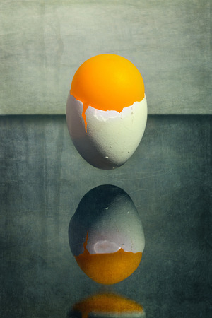 Eggshell stuck in the air above the table with an orange ball, surreal still life Morning