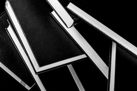 Books piled on top of each other, black and white photography.