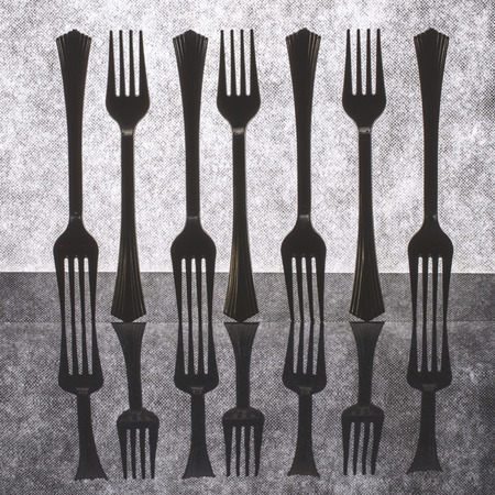 Very simple still life with forks on gray background