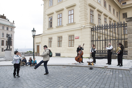 Prague, Czech Republic - June 06, 2013: Tourists from different countries dance to the music of street musicians