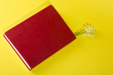 Red notepad with lily of the valley flowers on a yellow background