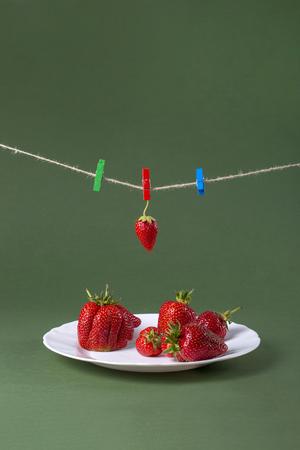Ripe strawberries on white plate and clothespins Archivio Fotografico