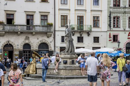 Lviv, Ukraine - August 13, 2019: People have a rest near the Neptune Fountain on Rynok Square in the center of Lviv