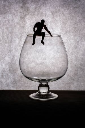 Silhouette of a man sitting on a large glass