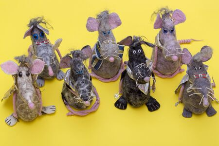 Soft toys made of felted wool on a yellow background