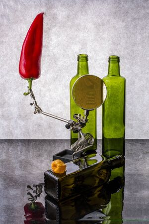 Still life with red pepper and glass bottles.