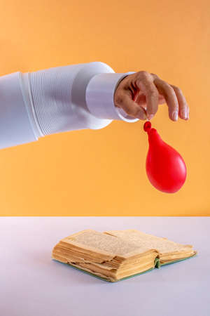 Man's hand with a deflated balloon over a book