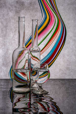 Still life with a figure from colored paper and glassware