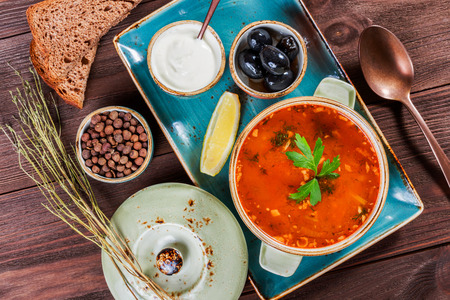 solyanka: Soup with meat, olives, herbs, lemon, sour cream in bowl, black bread and spices on dark wooden background, homemade food. Traditional Russian soup - solyanka. Top view Stock Photo