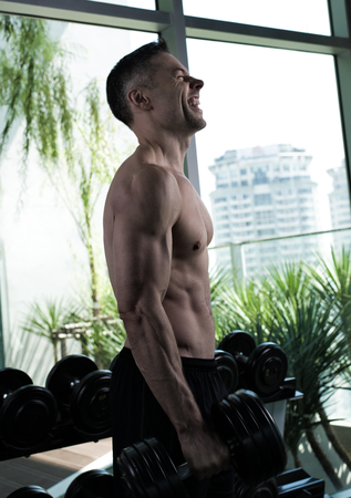 lean over: fit man over 40 working out in gym Stock Photo