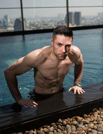 fits in: fit man over 40 posing by the pool Stock Photo