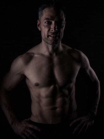 lean over: fit man over 40 on dark background