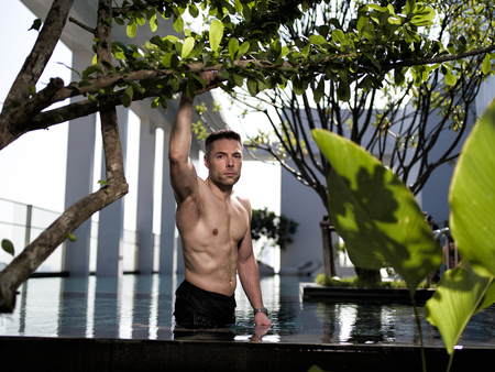 lean over: fit man over 40 posing in the pool Stock Photo