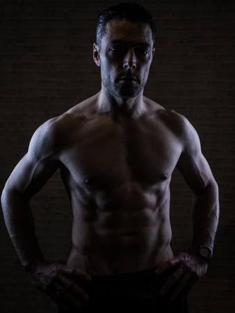 sixpack: fit man over 40 on dark background