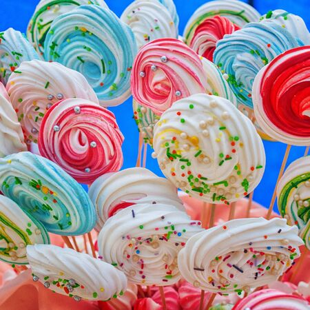 Many delicious multi-colored cakes on sticks