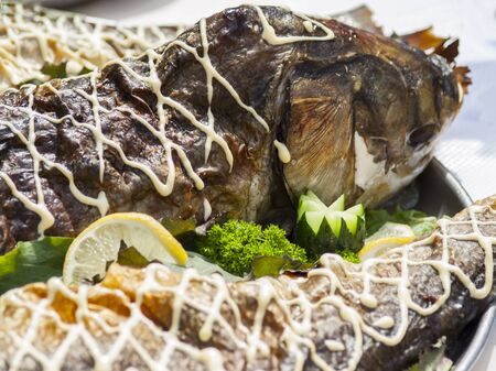 Stuffed fish on a tray with greens and lemon