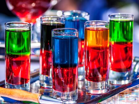 Red, blue, yellow, green and black drinks of different densities and poured into glass containers