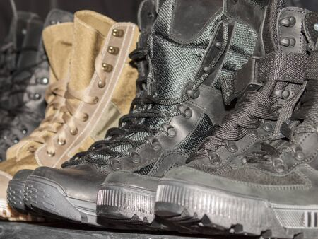 New army waterproof boots of different colors and sizes close-up