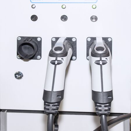 The panel with two pistols for charging electric vehicles close-up