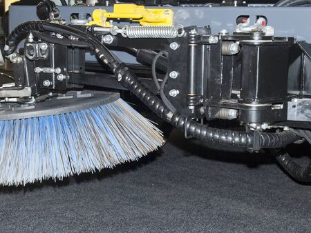 Close-up tractor metal brush nozzle for street cleaning