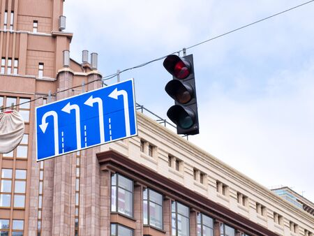 Traffic signs indicating the direction of movement and traffic light on the background of a large building