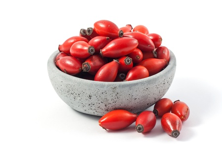 A bouquet of rosehips on a bowl on white background
