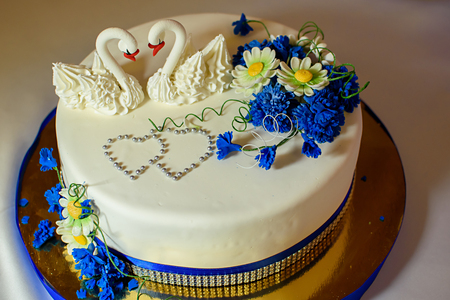 Festive white cake decorated with white swans