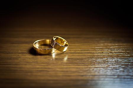 Gold wedding rings on a wooden table Foto de archivo
