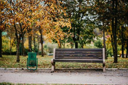 An urn next to an empty park bench.