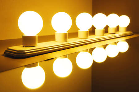 A group of incandescent lamps and their reflection in the mirror