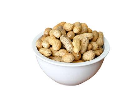 nutshell: A white dish full of peanuts in nutshell
