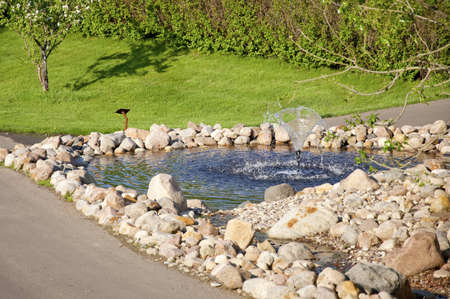 Decorative small  fountain whith blue water Stock Photo