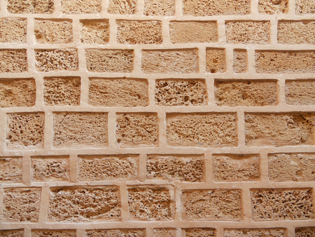 Stone wall background, close-up of porous blocks in the masonry, stone wall made of porous limestone blocks, part of old stone wall in Jaffa, Israel Banco de Imagens