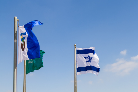 HERODIUM, ISRAEL - JULY 13, 2018: Flags of in the wind, National flag of Israel with Star of David, flag of the Israel Nature and Parks Authority and Army flag with symbol in Herodium, Israel